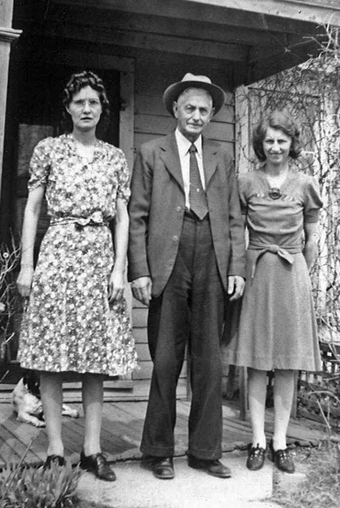 Mrs. Roberts (Grandpa's housekeeper), Grandpa, and his niece Verna Noble Bowhan on the front porch of Grandpa's house, which was built around a train car.
